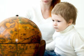 Baby playing with earths globe — Stock Photo