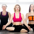 Group of three females meditating in class — Stock Photo #65625889