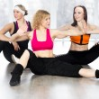 Group of three females doing dynamic fitness exercises in class — Photo #65625901