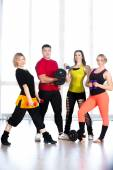 Group of sporty people holding dumbbells in gym — Stockfoto