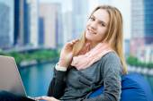Young girl using laptop in comfy armchair with big city on the b — Stock Photo
