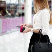 Mujer joven en ropa de moda busca en una carpeta en sho — Foto de Stock