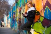 Runner girl with smartphone before morning jogging — Stock Photo