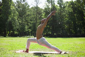 Crescent yoga pose in park — Stock Photo