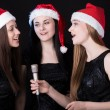 Three attractive young women singing — Stock Photo #77700848