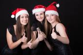 Three attractive santa girls with microphone showing thumbs up — Stock Photo