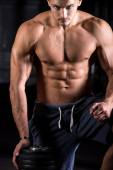 Tough young bodybuilder in gym — Stock Photo