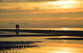 Silhouette of a couple walking along the beach at sunset in Jurmala, Latvia — Stock Photo