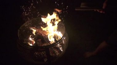 Hand throws wood onto backyard fire pit, slow motion (240 fps) — Stock Video