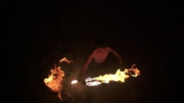 Skilled fire dancer looks up at camera, throws fire staff toward camera and catches it, performs fire spinning, top down shot, slow motion (60 fps) — Stock Video