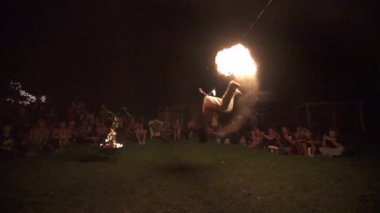 Skilled fire dancer performs fire breathing backflip then breaths fire into air again, slow motion (240 fps) — Stock Video