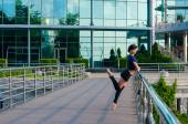 Ballet dancer in casual clothes standing on tiptoes operands hands on railing — Stock Photo