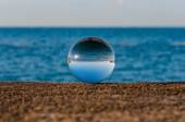 Glass transparent ball on sea background and grainy surface. Water — Stock Photo