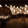 Glass transparent ball and burning candles on old wooden background — Stock Photo #71135227