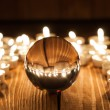 Glass transparent ball and burning candles on old wooden background — Stock Photo #71134865