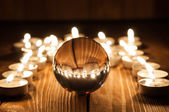 Glass transparent ball and burning candles on old wooden background — 图库照片