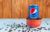 Kiev, Ukraine, April 2015. Can Pepsi cola in a bowl of coffee standing on blue table, dark wooden background with empty space. Carbonated soft drink that produced and manufactured by PepsiCo. Created — Stockfoto