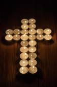 Lit tea lights in the shape of a cross on old wooden background — Stock Photo