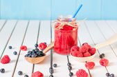 Healthy diet high dietary fiber breakfast with blueberries and raspberries in mason jar on aqua blue rural wooden background. — Stock Photo