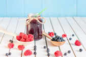 Blackberries jam in mason jar and fresh raspberry, blueberry on a wooden table. Macro image, selective focus — Stock Photo