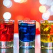 Berry alcoholic drink into small glasses on bar desk with magic illumination bokeh background — Stock Photo #79856664
