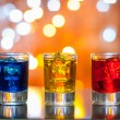 Berry alcoholic drink into small glasses on bar desk with magic illumination bokeh background — Stock Photo #79936086