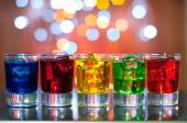 Berry alcoholic drink into small glasses on bar desk with magic illumination bokeh background — Stock Photo