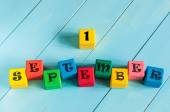 First September sign on color wooden cubes with light blue wood background. Back to school time — Stock Photo