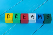 Dreams - word on childrens colourful cubes or blocks. Colourful wooden background — Stock Photo