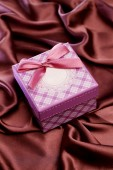 Gift box isolated on satin cloth — Stock Photo
