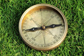 Old directional compass on green grass — Stockfoto