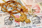 Gold ornaments on Indian currency — Stock Photo