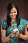 Smiling young traditional woman text messaging — Stock Photo
