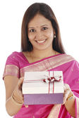 Happy young Indian traditional woman holding gift box in hands — Stock Photo