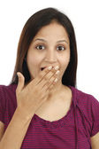 Young woman with hand over mouth — Stock Photo