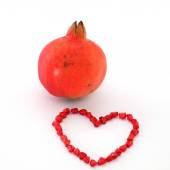 Pomegranate and seeds arranged in heart shape — Stock Photo