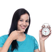 Happy young woman showing old style antique alarm clock — Stock Photo