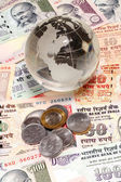 Glass globe on Indian currency — Stock Photo