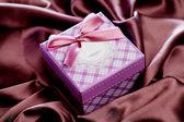 Подарочная коробка изолирована на атласной ткани — Стоковое фото