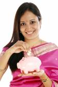 Young Indian traditional woman inserting a Indian ten rupee coin — Stock Photo