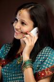 Young traditional woman talking on cellphone — Stock Photo