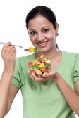 Young Indian woman eating fruit salad against white — Stock Photo