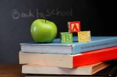 ABC blocks and apple against black board — Stock Photo
