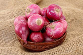 Red onions in wooden bowl — Stock Photo