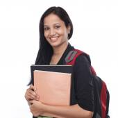 Happy young female student with books and backpack — Stock Photo