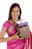 Excited young traditional woman holding gift boxes — Stock Photo