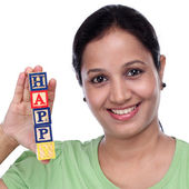 """Young woman holding wooden blocks of word """"Happy"""" — Stockfoto"""