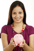Young Indian woman holding a piggy bank — Stock Photo