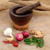 Wooden mortar with various spices on sacking — Stock Photo