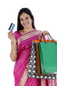 Smiling Indian woman with shopping bags and credit card — Stock Photo